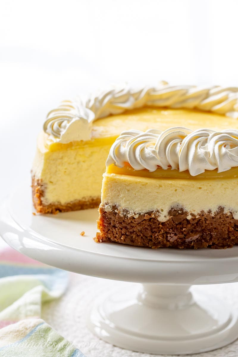 A sliced cheesecake on a cake stand with a lemon curd topping