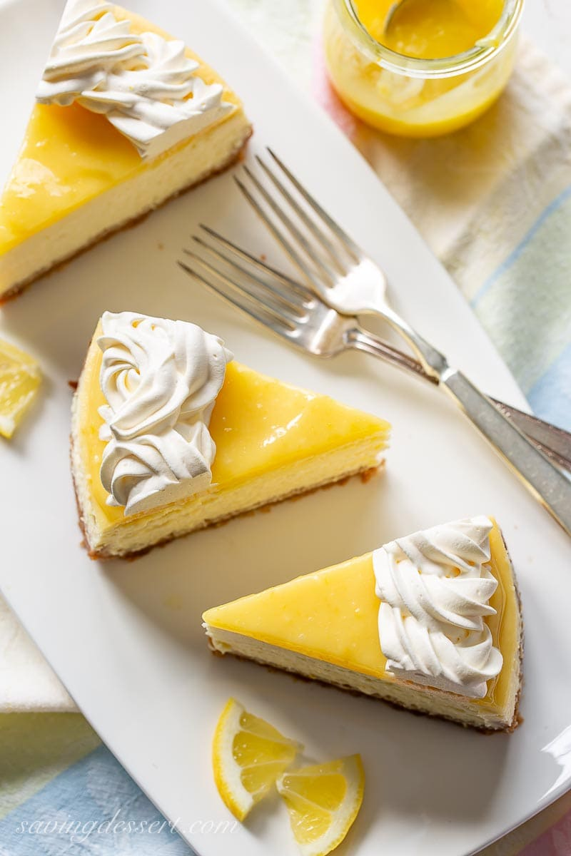 Slices of lemon cheesecake on a platter with a whipped cream topping