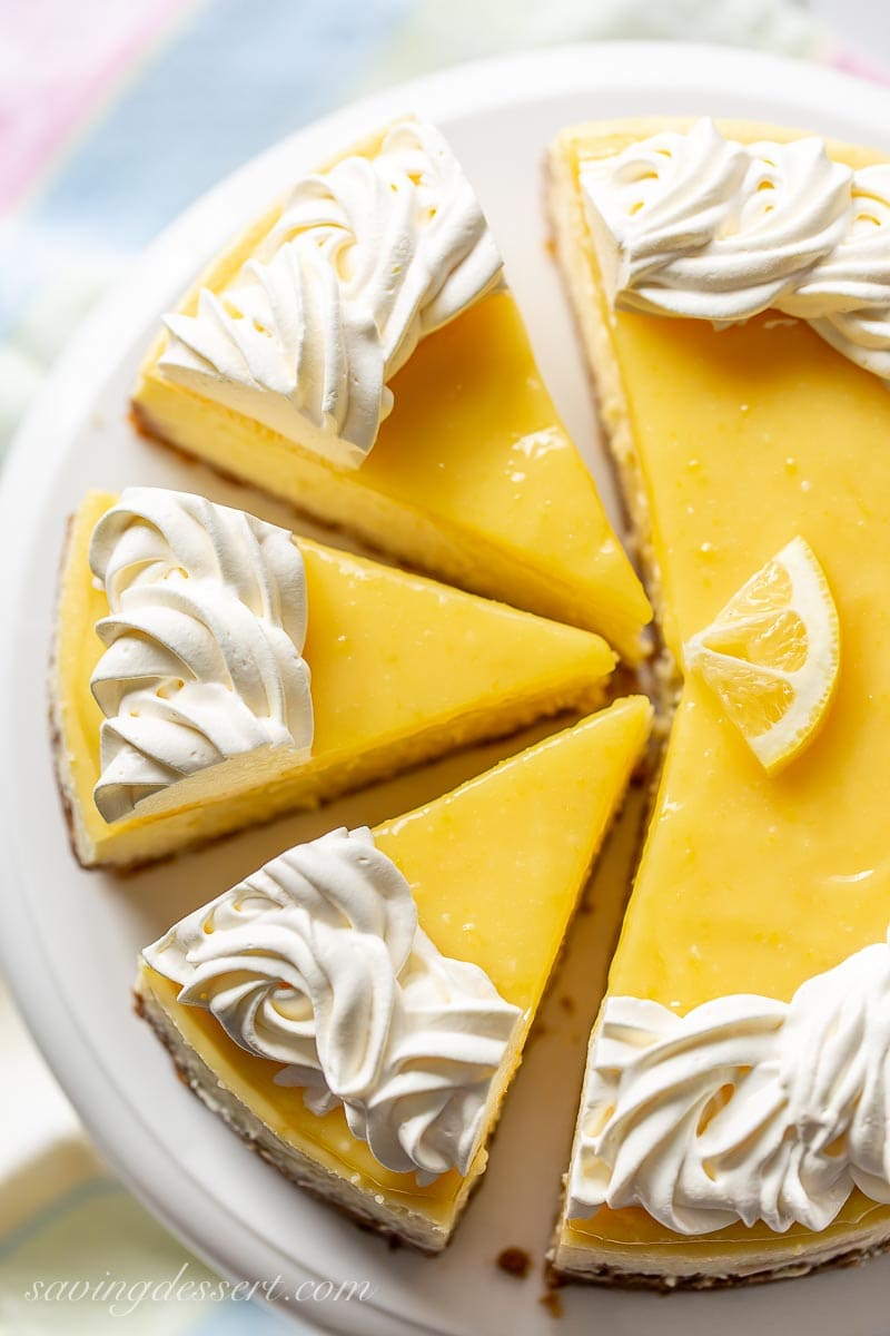 An overhead view of a sliced lemon curd topped cheesecake