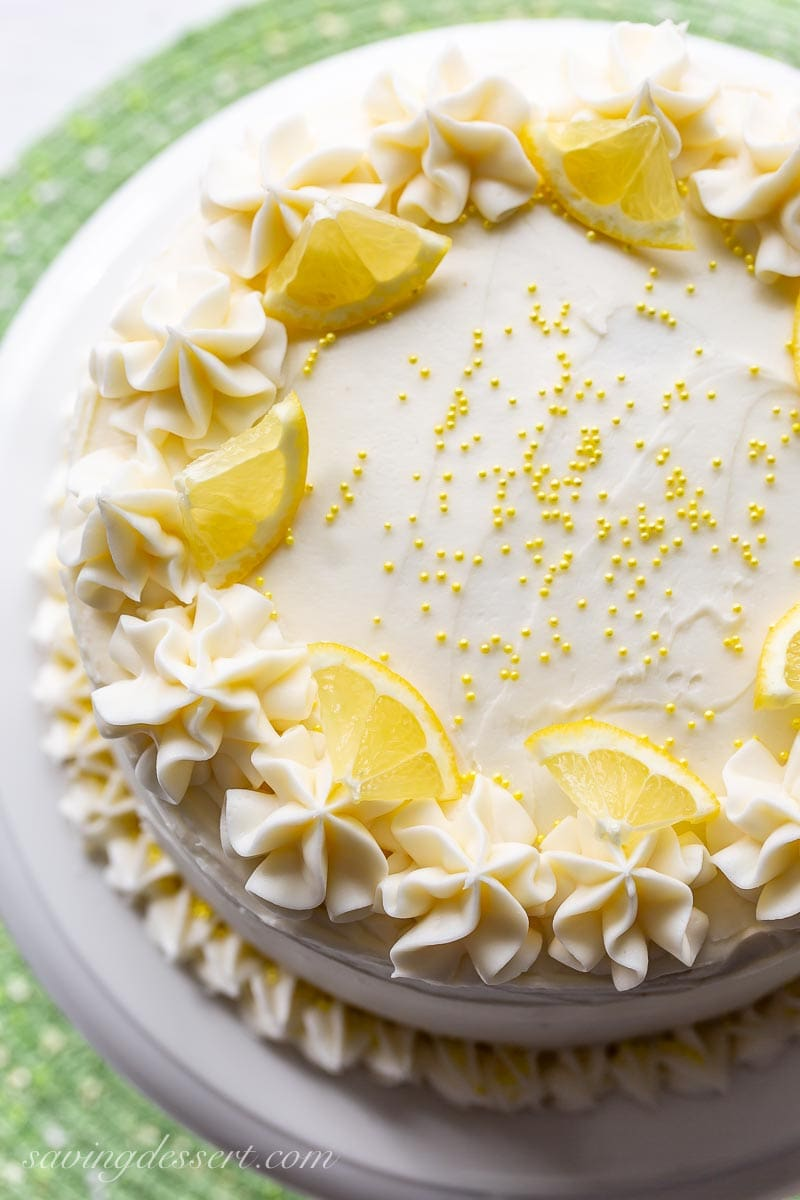 An overhead view of a lemon layer cake topped with yellow sprinkles