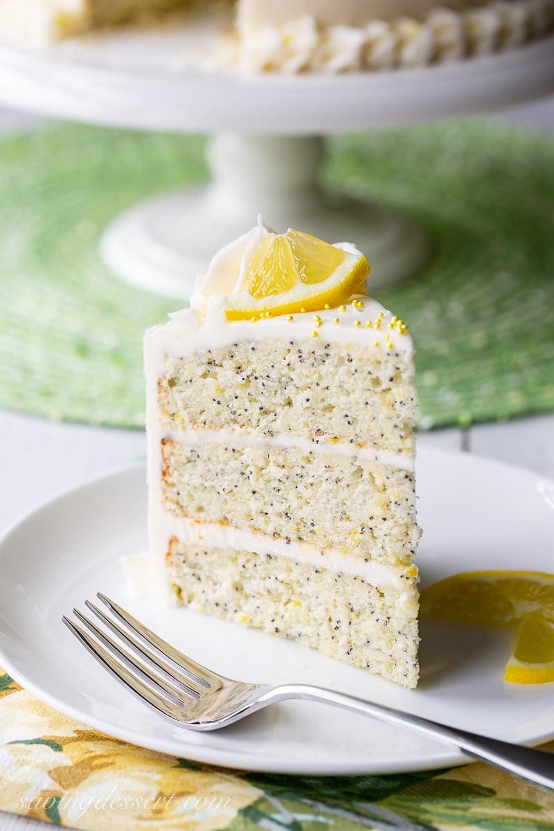 A slice of lemon poppy seed cake on a plate with a fork