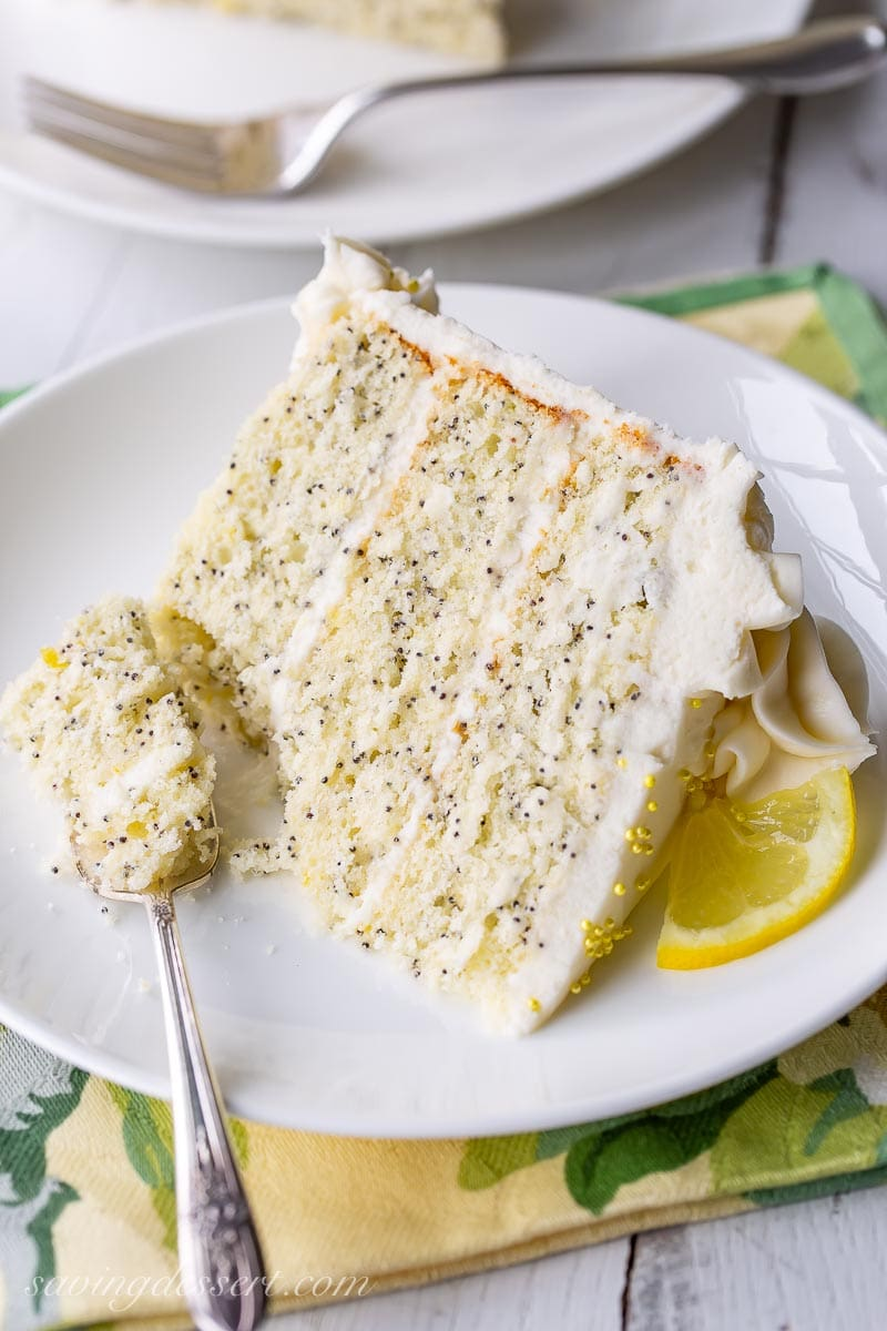 A slice of lemon poppy seed cake garnished with a sliced lemon