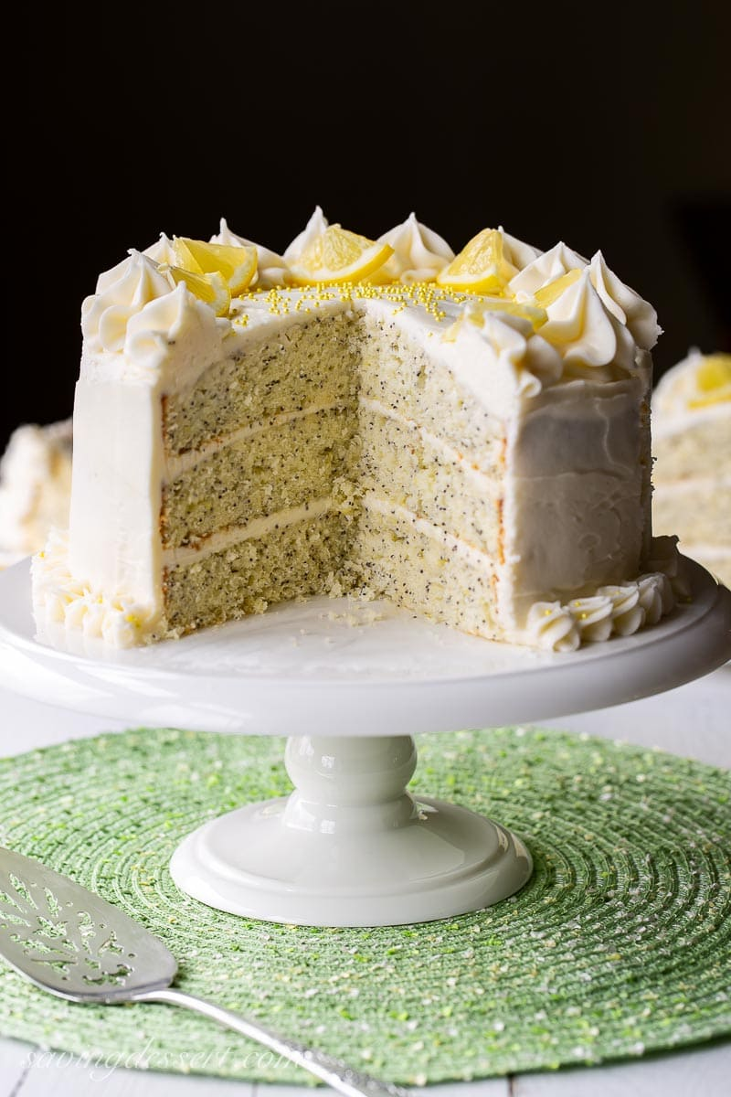 A sliced three layer lemon poppy seed cake with lemon cream cheese icing