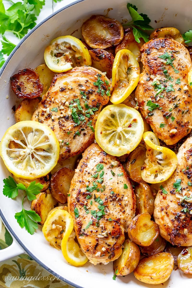 A skillet filled with chicken breasts, roasted potatoes and lemon slices