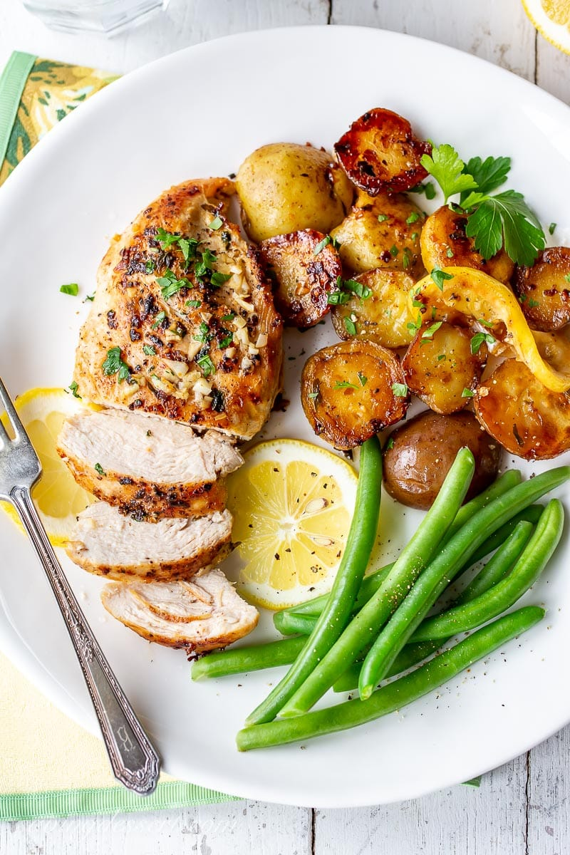 A plate of chicken, potatoes, green beans and lemon