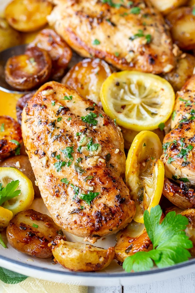 A close up of chicken breasts garnished with parsley and lemon slices