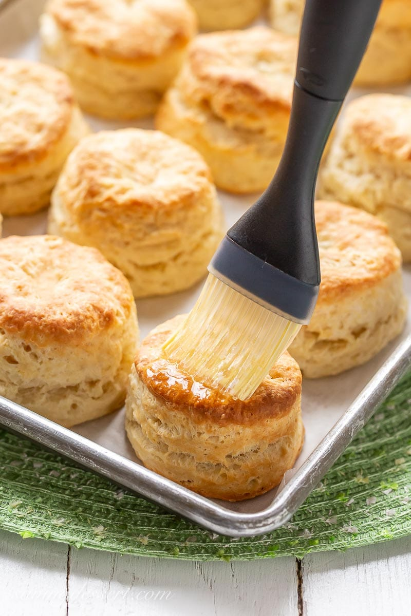 A baking pan filled with hot, golden brown buttermilk biscuits brushed with melted butter