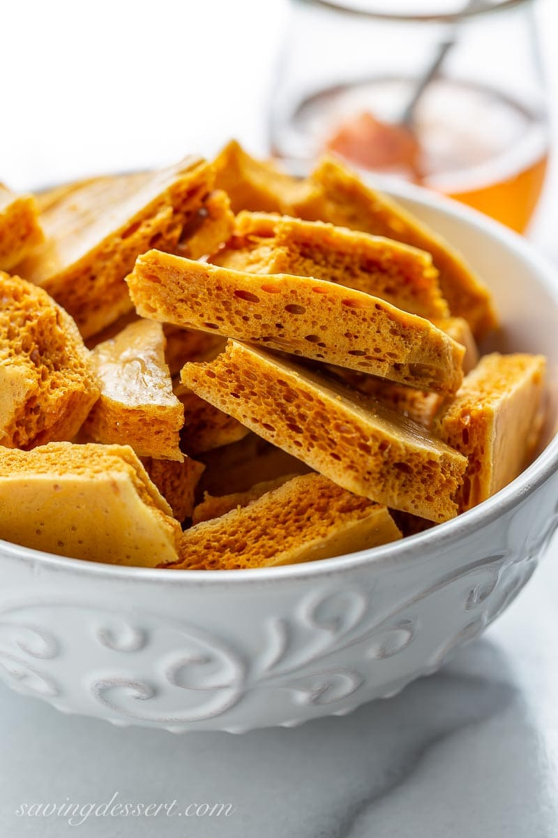 A closeup of honeycomb candy in a bowl, with an airy texture and deep golden color