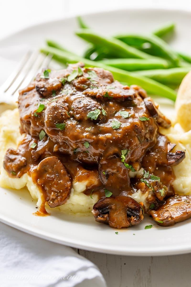 Un piatto con la bistecca alla Salisbury servita sopra un purè di patate con fagiolini