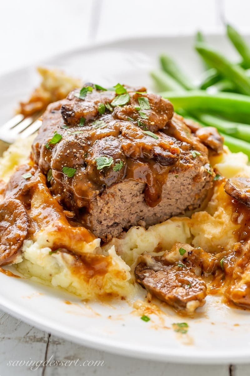 A plate of mashed potatoes with Salisbury Steak and green beans