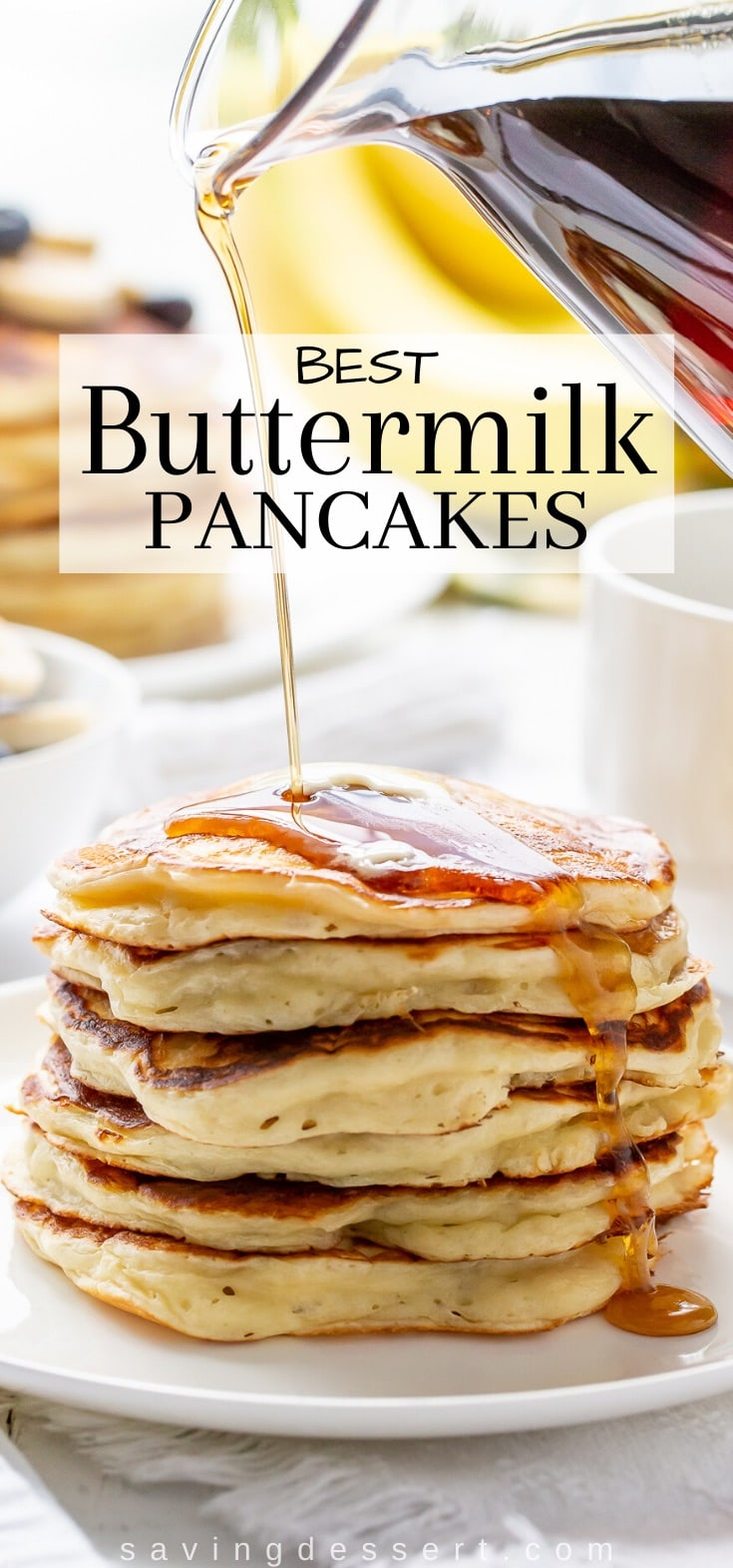 A stack of buttermilk pancakes with maple syrup poured over the top