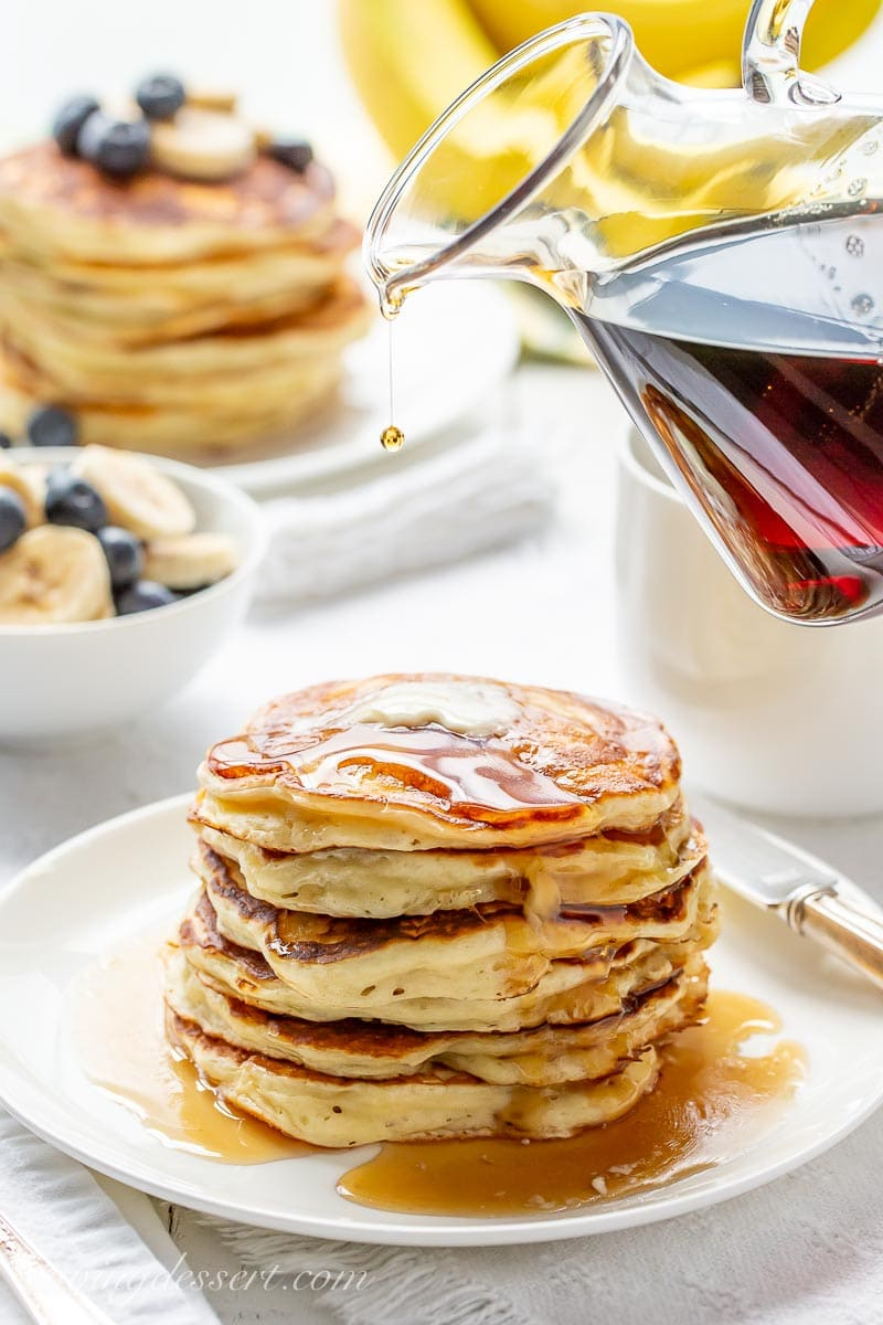 A stack of pancakes drizzled with maple syrup