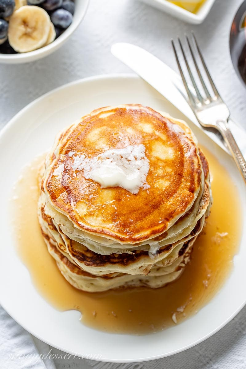 An overhead view of buttermilk pancakes with a pat of butter on top