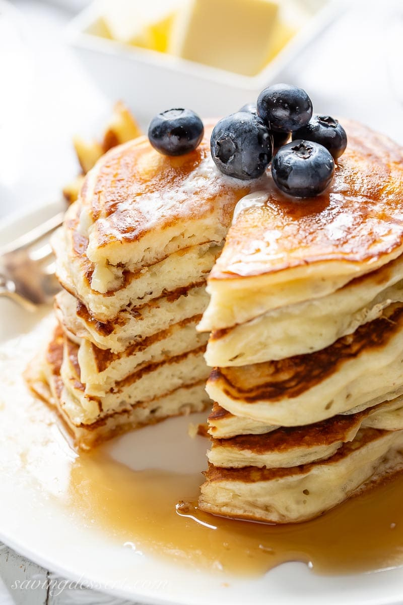 A stack of sliced buttermilk pancakes with blueberries on top