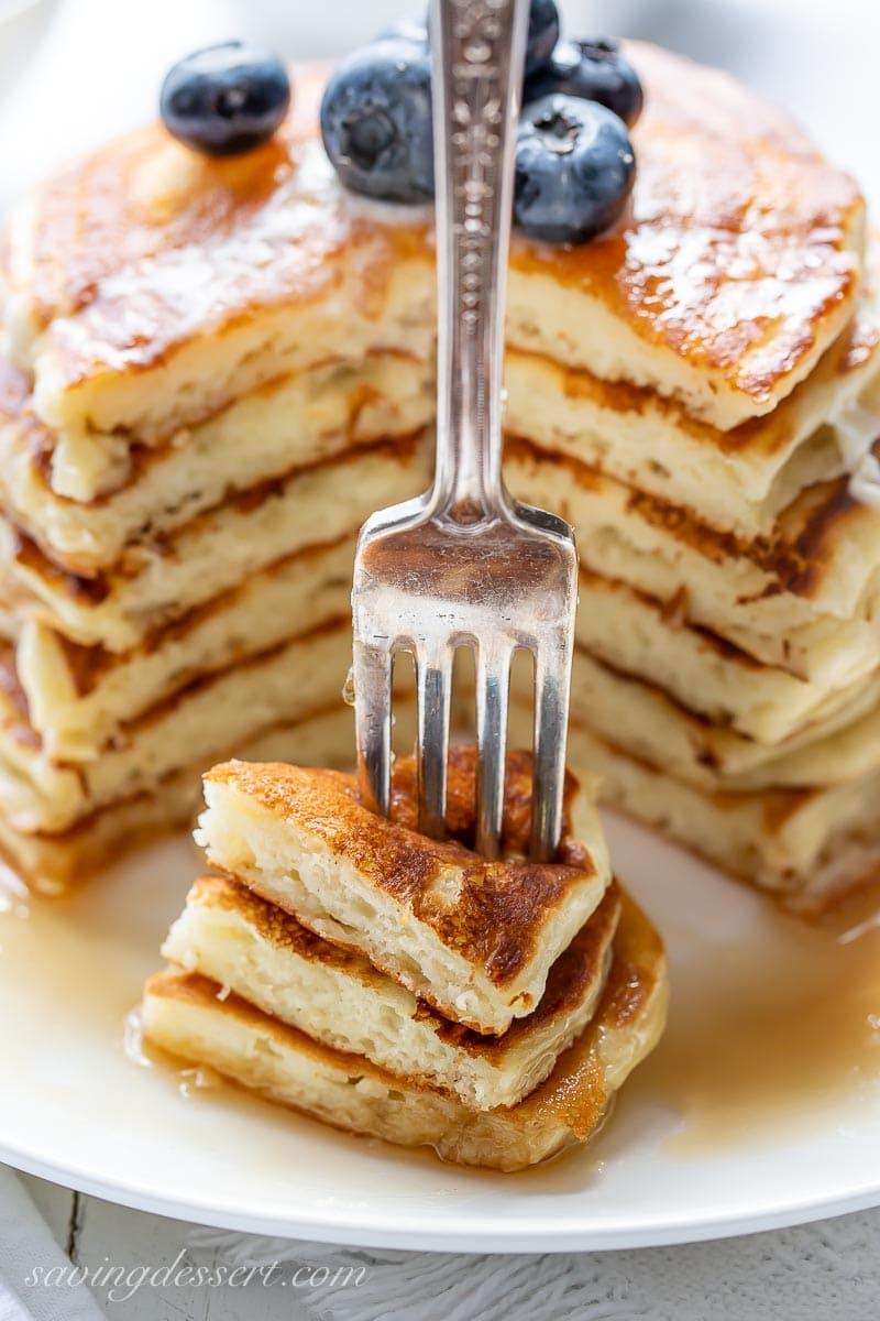 A fork full of fluffy buttermilk pancakes