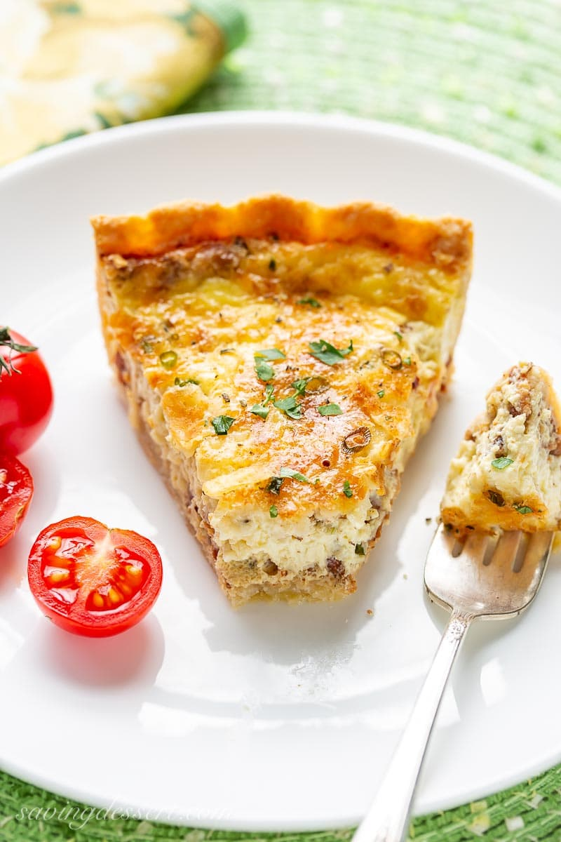 A pice of quiche on a plate with sliced tomatoes