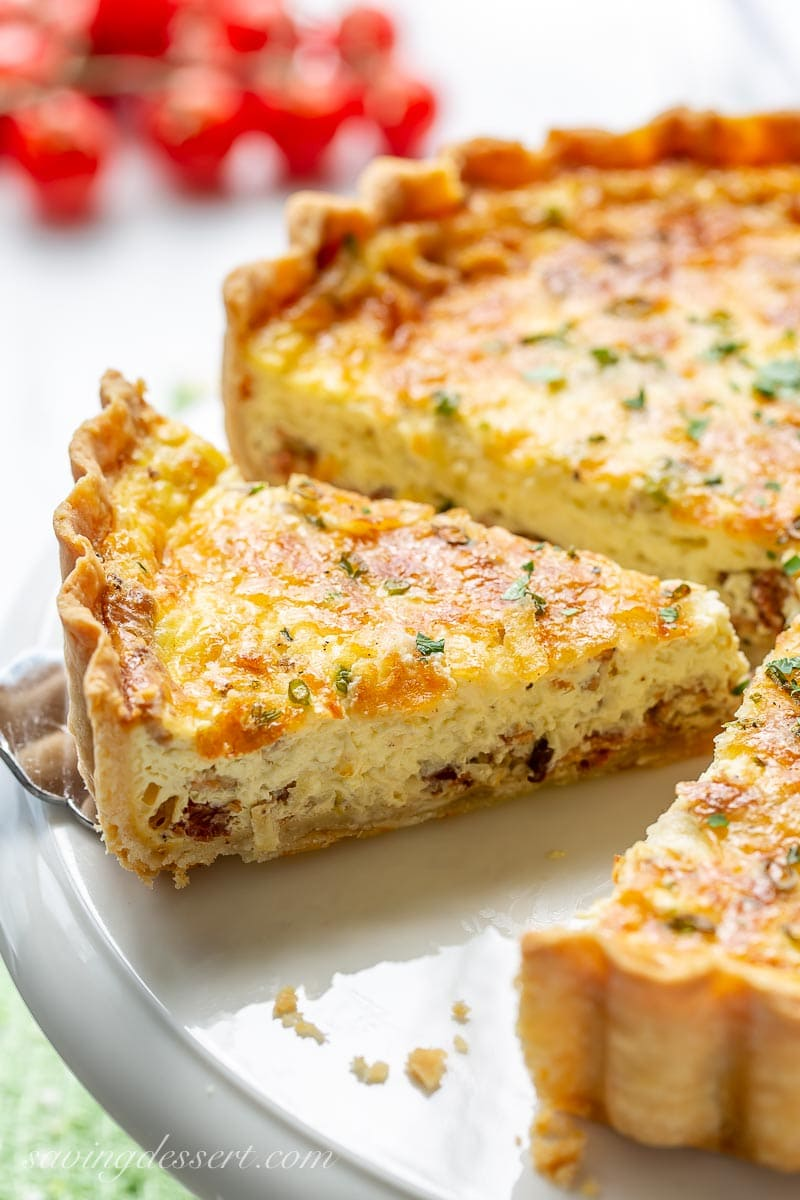 A sliced quiche on a cake platter