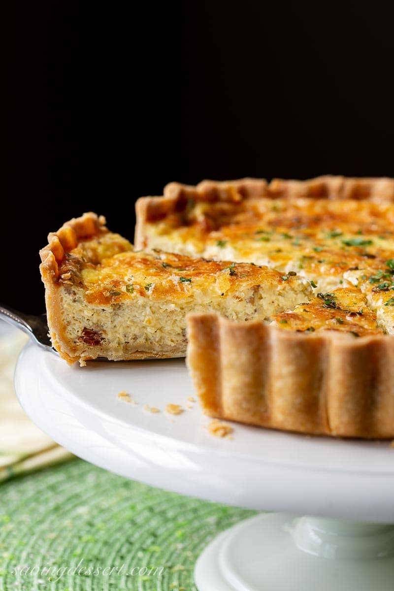 A sliced quiche on a cake stand