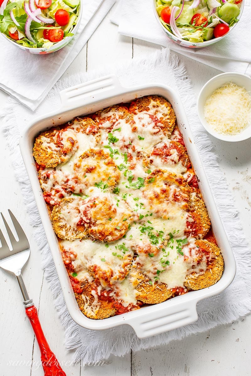 A casserole dish with eggplant Parmesan topped with mozzarella and chopped parsley. Served with extra Parmesan on the side and salad