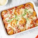 A casserole dish filled with eggplant Parmesan topped with melted mozzarella cheese
