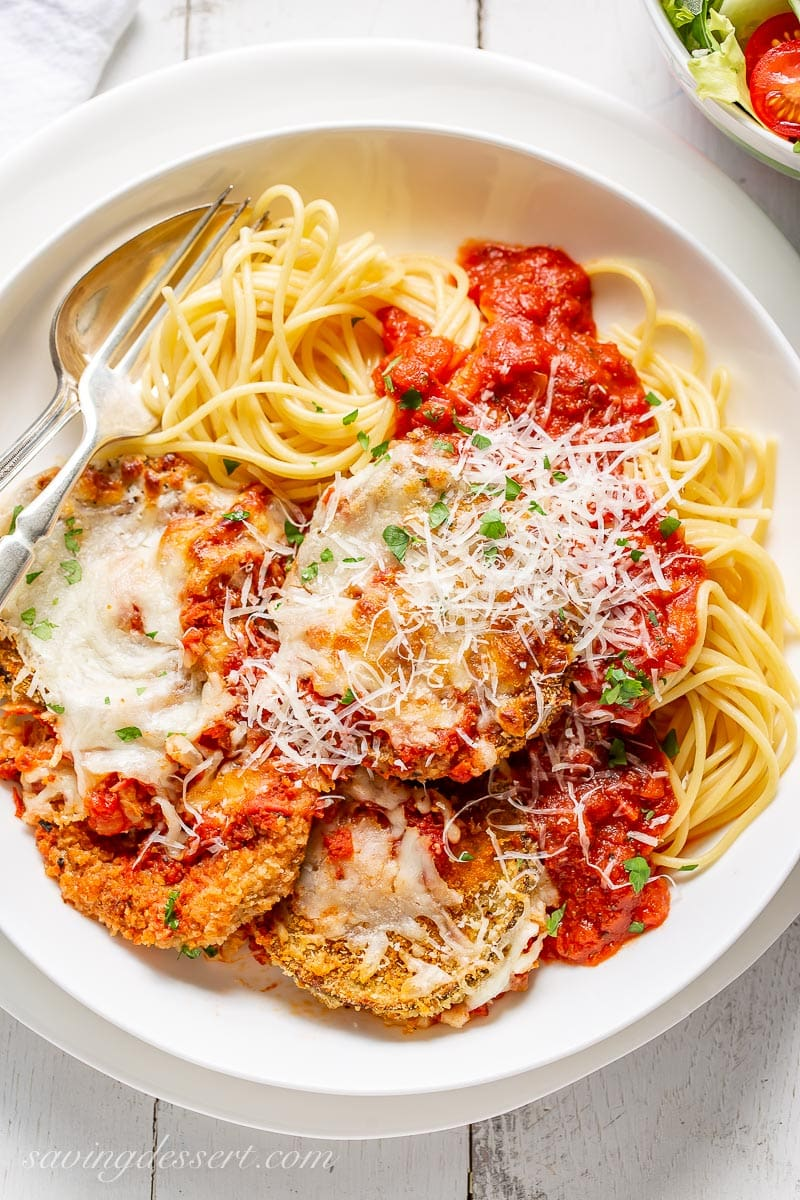 An overhead view of a bowl of spaghetti with marinara sauce and eggplant Parmesan