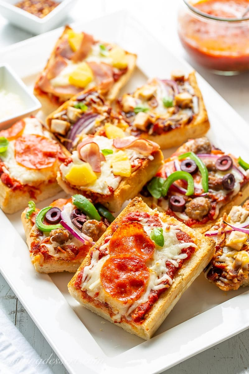 A platter filled with a variety of French bread pizzas