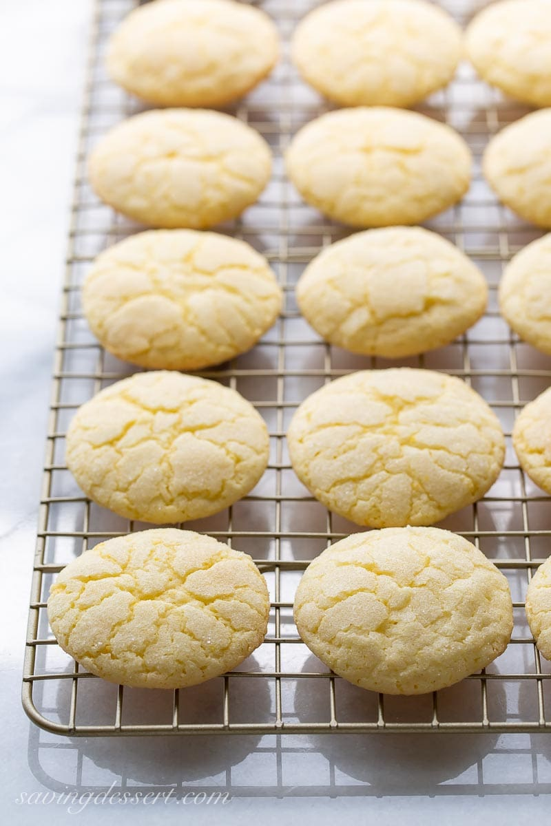 A cooling rack stacked with lemon cookies