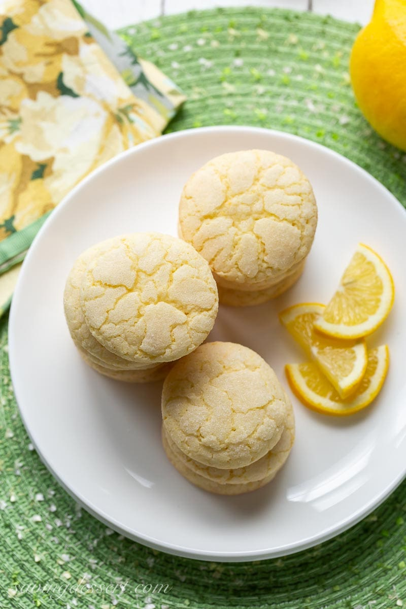 An overhead view of a plate of lemon cookies with lemon wedges
