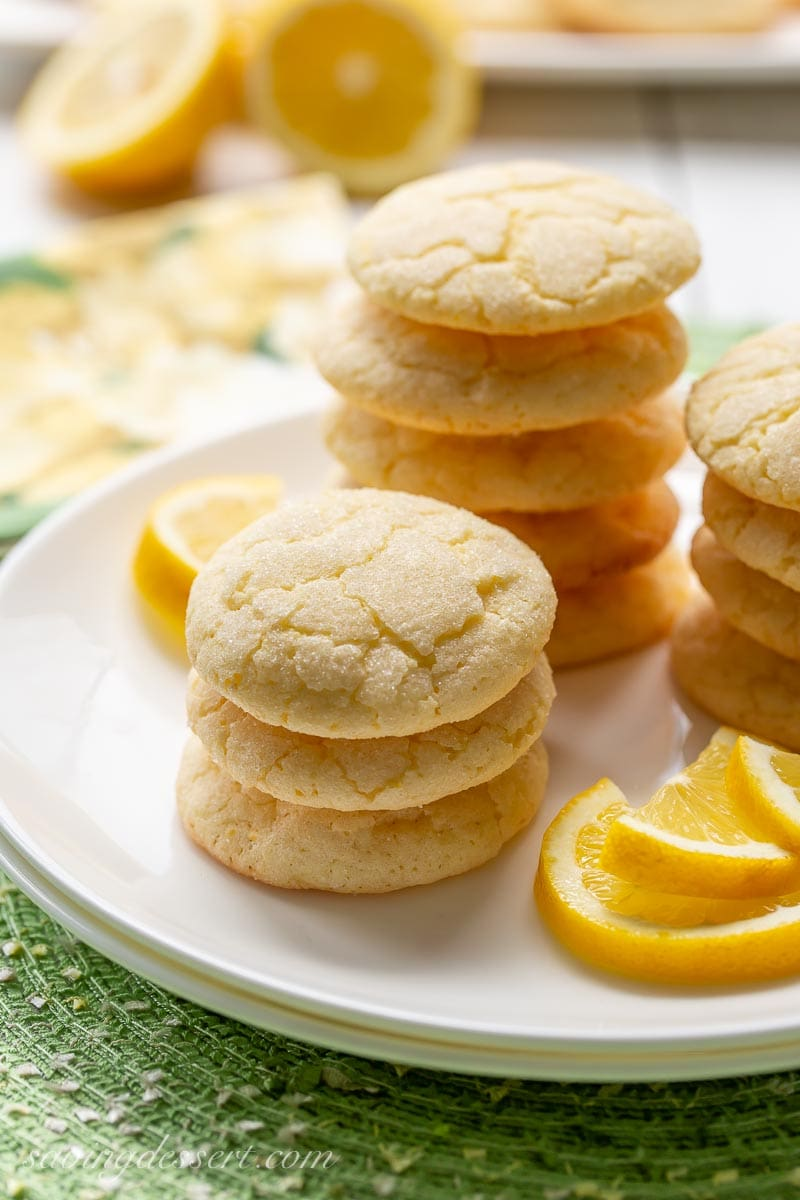 Stacks of lemon sugar cookies on a plate with lemon wedges on the side