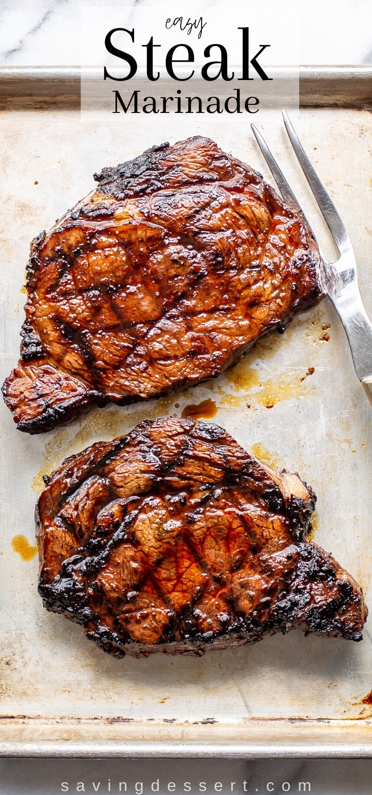 Two large, juicy grilled ribeye steaks on a small baking pan