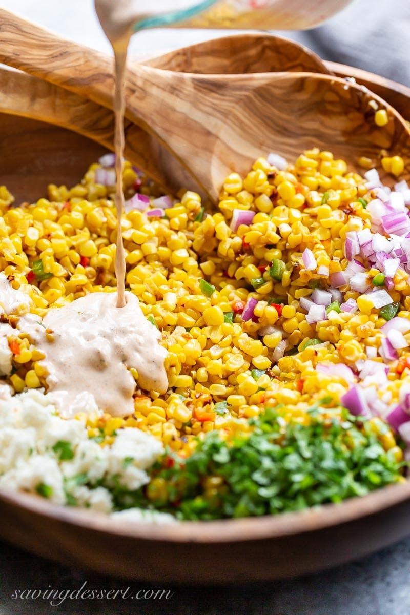 A wooden bowl of corn and onions being drizzled with a creamy dressing