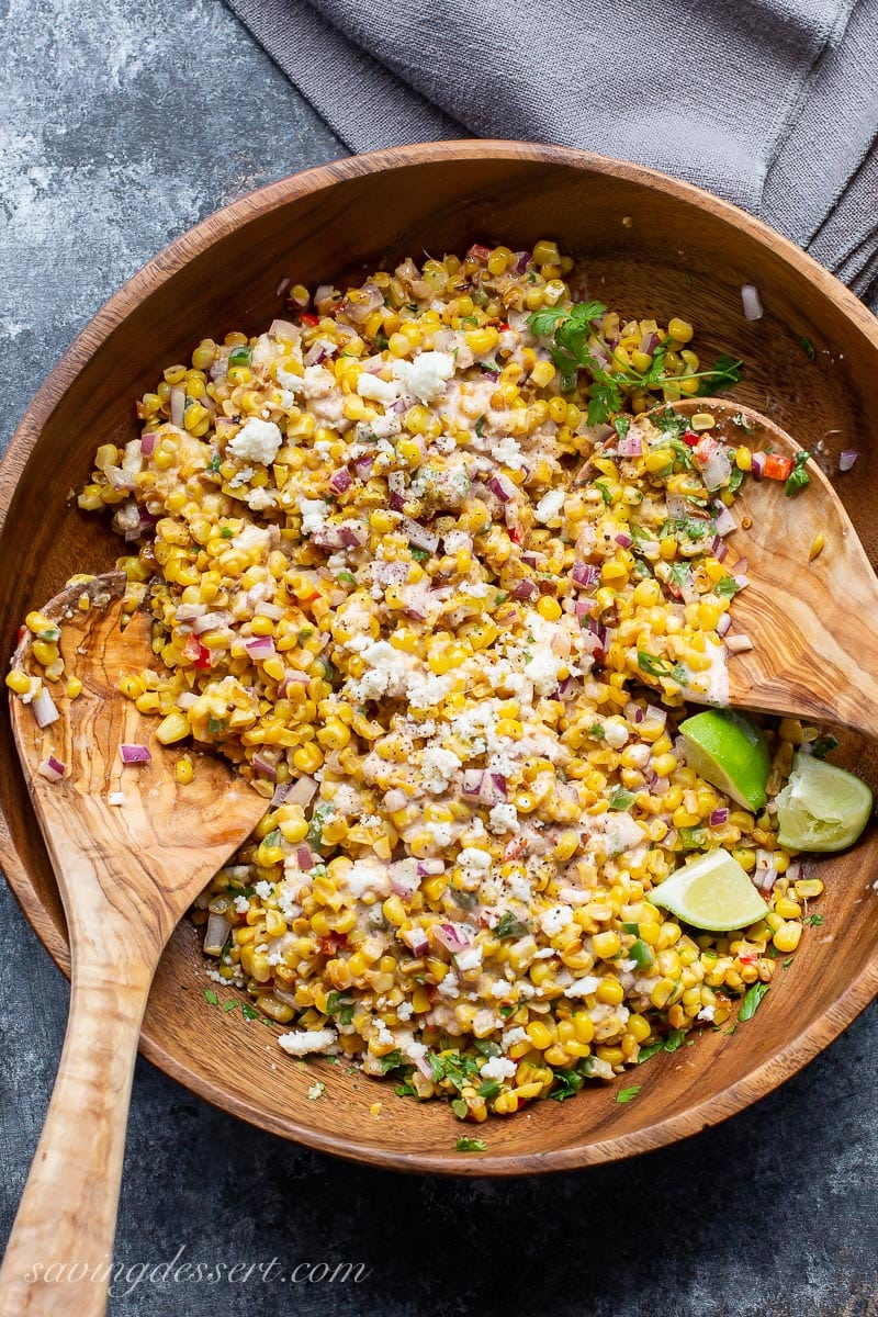 A bowl of Mexican Street Corn Salad tossed with crumbled cheese and lime wedges