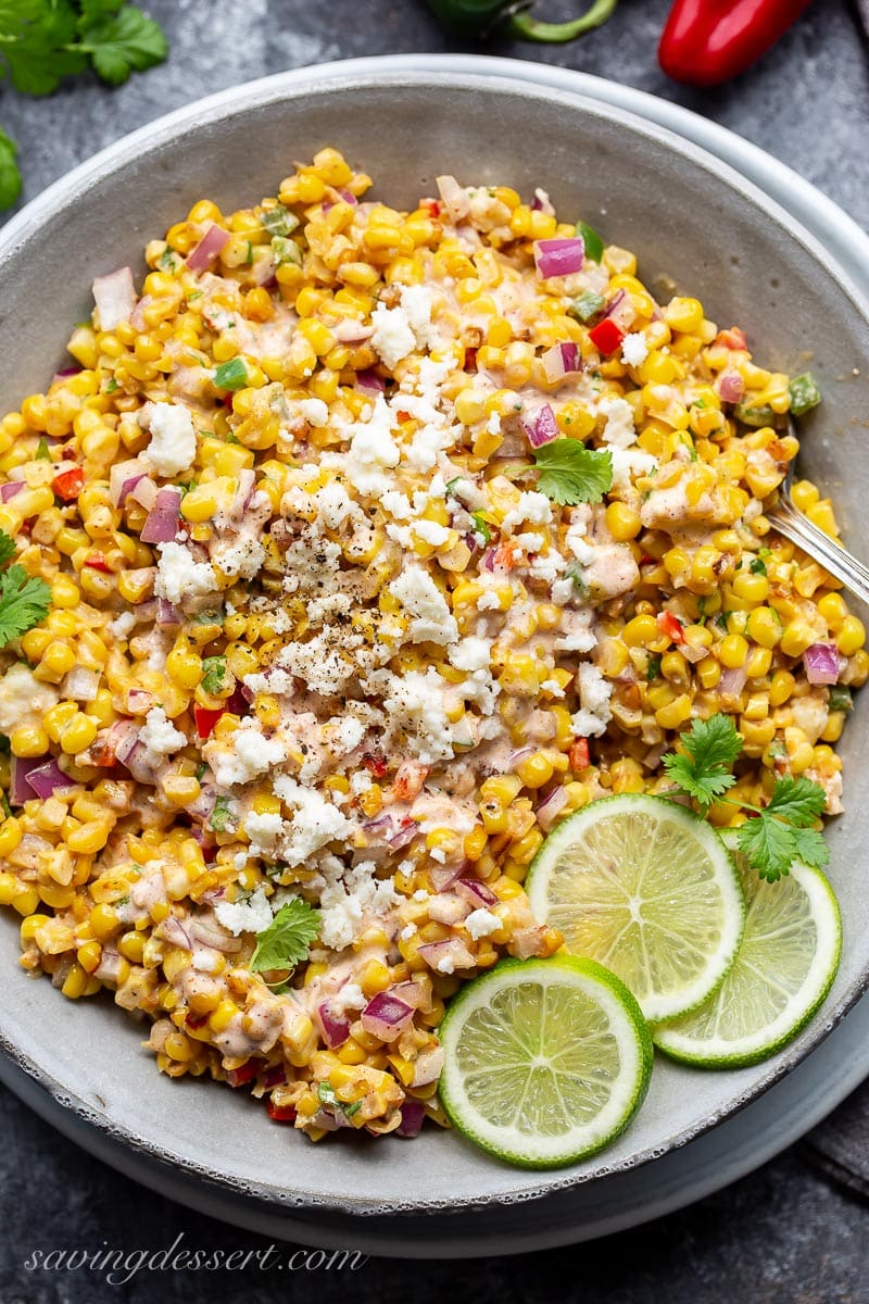 A bowl of charred corn tossed with onions, crumbled cheese, red peppers and lime juice