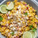 A bowl of corn salad garnished with cilantro, and fresh lime wedges