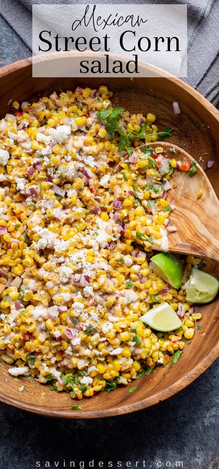 A closeup of a wooden bowl filled with a charred corn salad and a wooden spoon