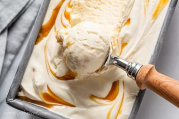 A pan filled with creamy caramel ice cream in a scoop