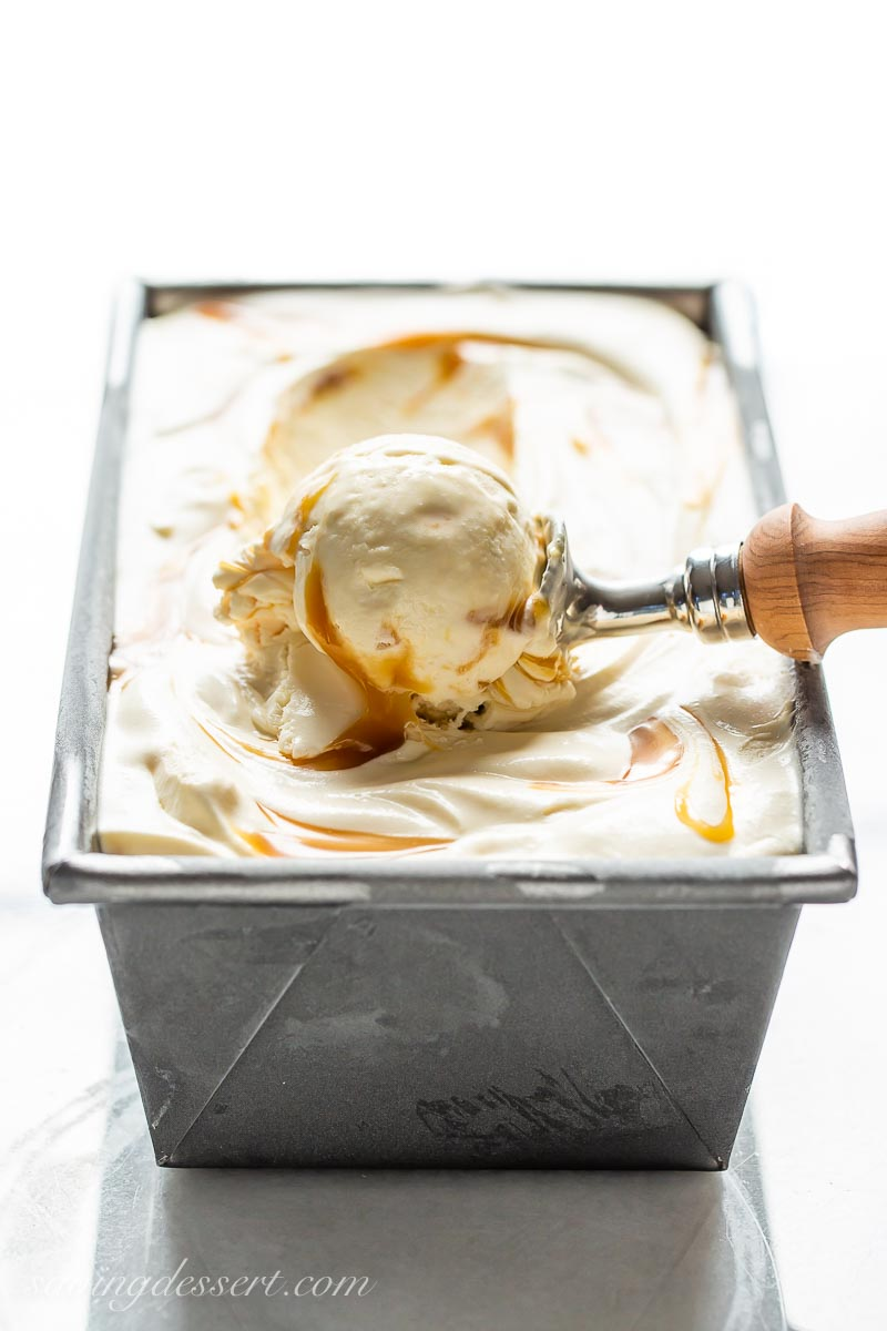 A view of a loaf pan from the side, showing a scoop of frozen vanilla in an ice cream scoop