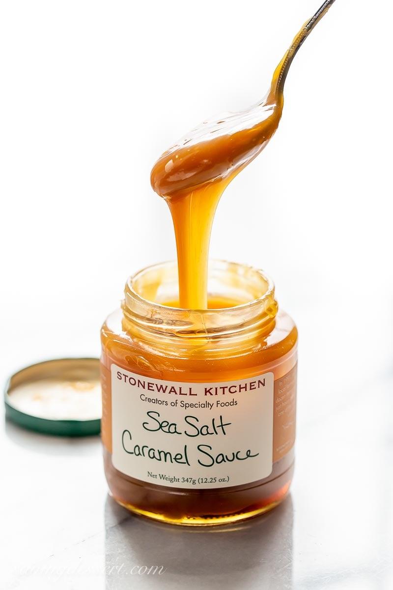 A jar of sea salt caramel sauce with a spoon drizzling caramel