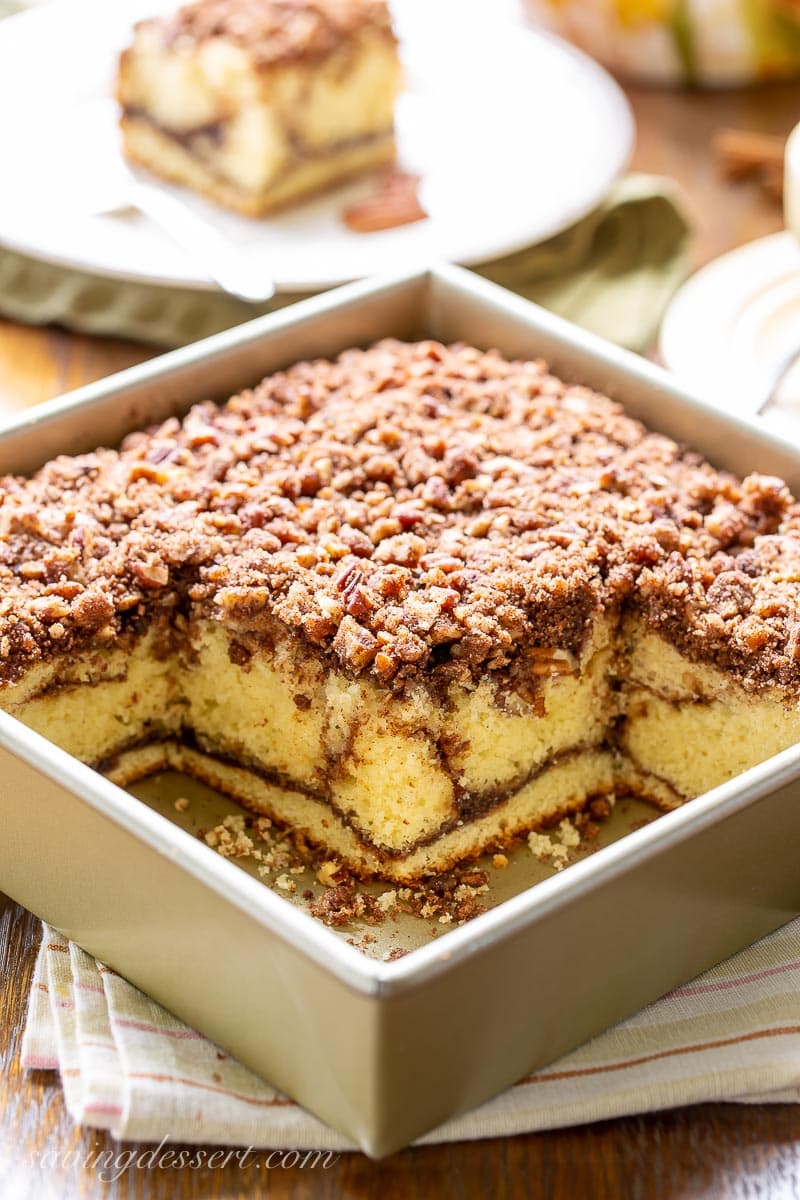 A square pan with sour cream coffee cake topped with pecan streusel
