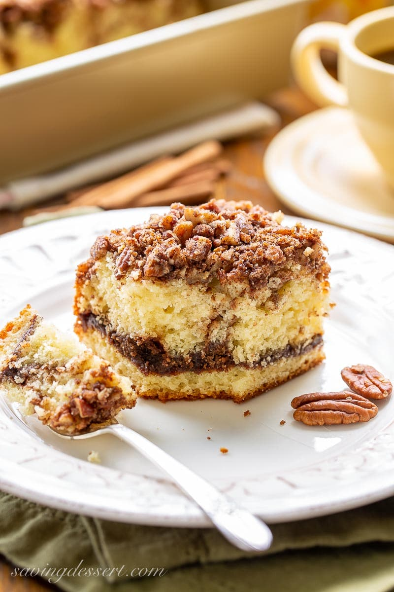 A fork full of cinnamon coffee cake with pecans