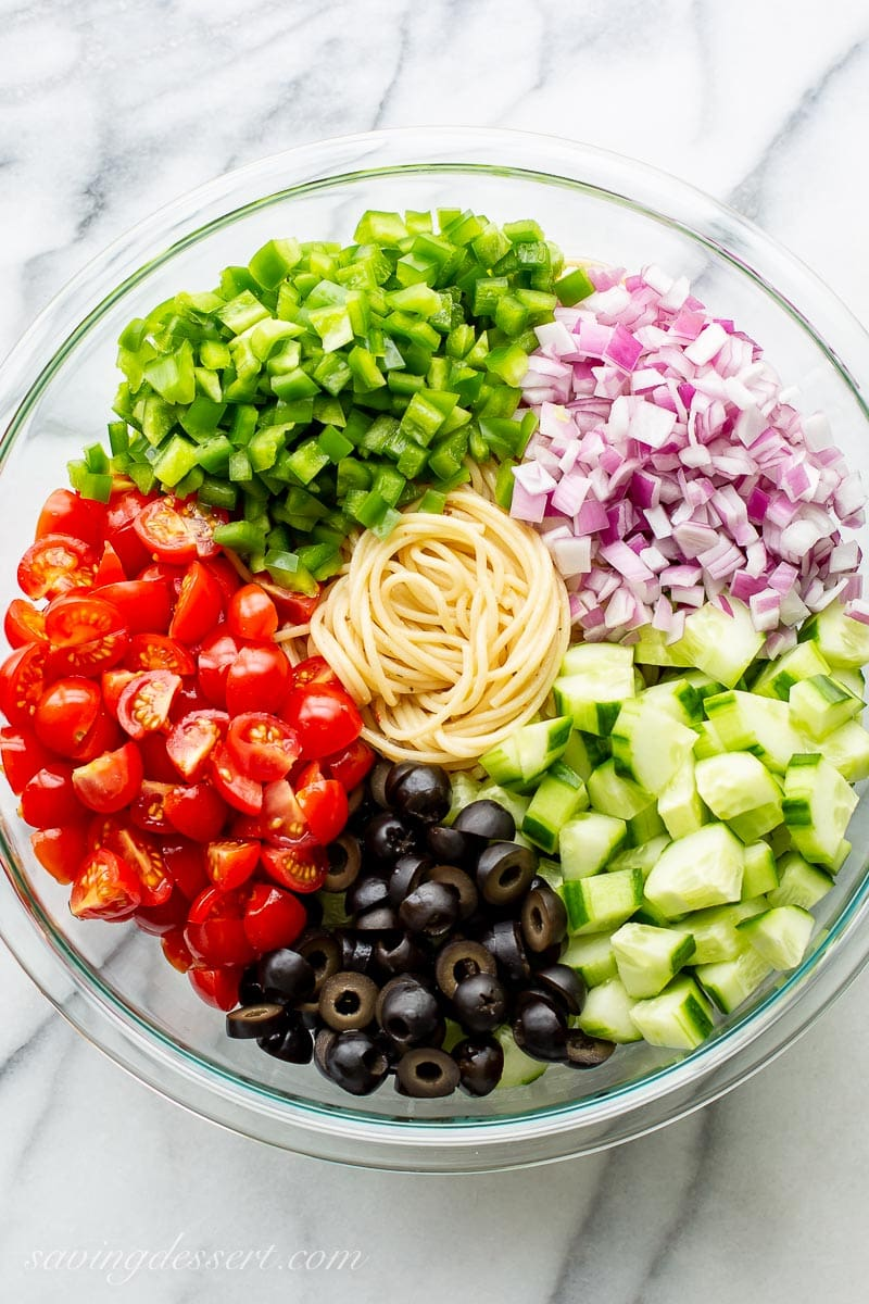 A large bowl filled with diced green bell pepper, red onion, cucumber, olives, tomatoes and spaghetti