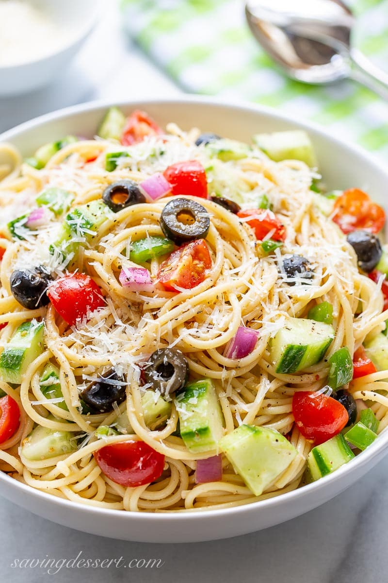 A bowl of cold spaghetti salad with tomatoes, cucumbers, black olives and green bell pepper