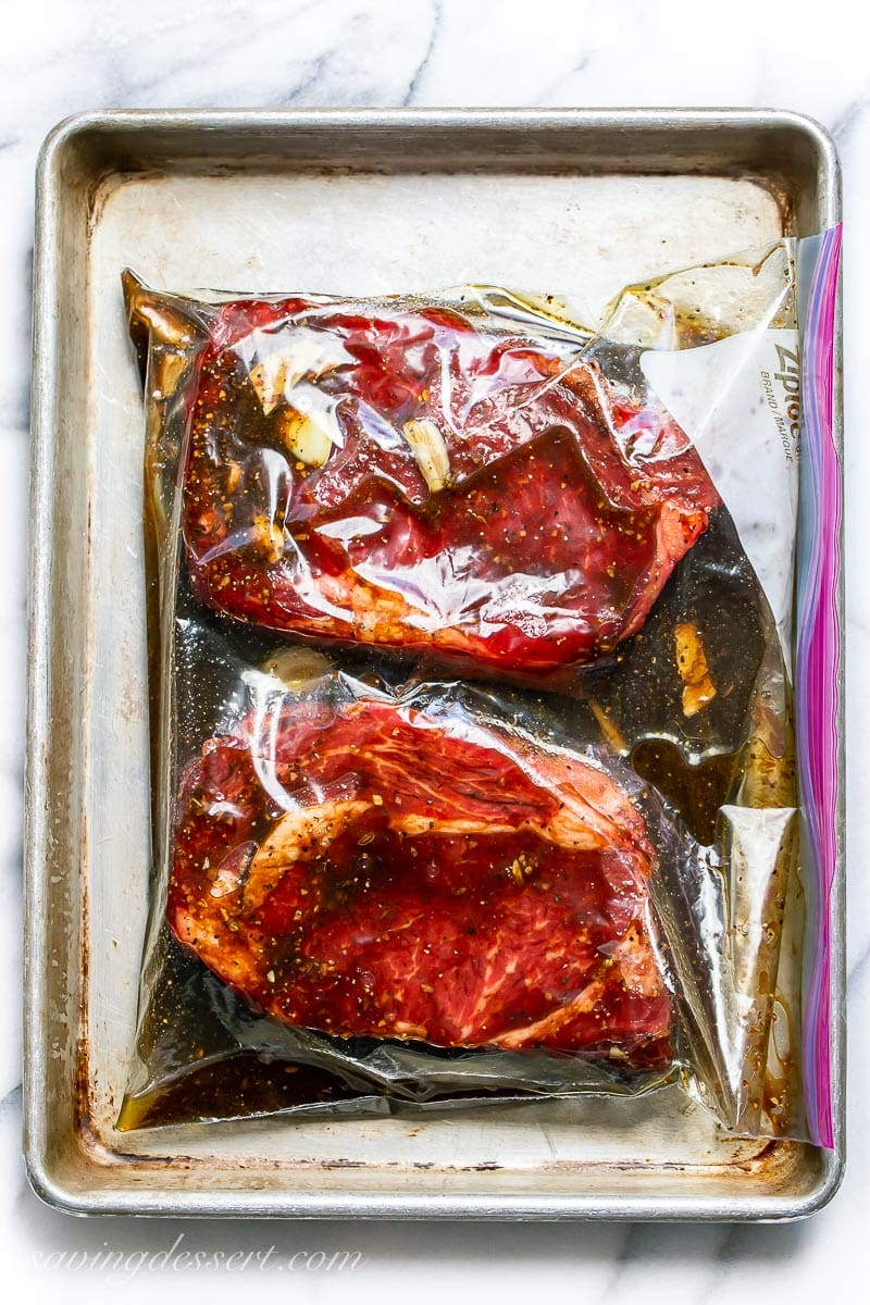 A large sealed zipper bag with two steaks in a dark marinade with cloves of garlic