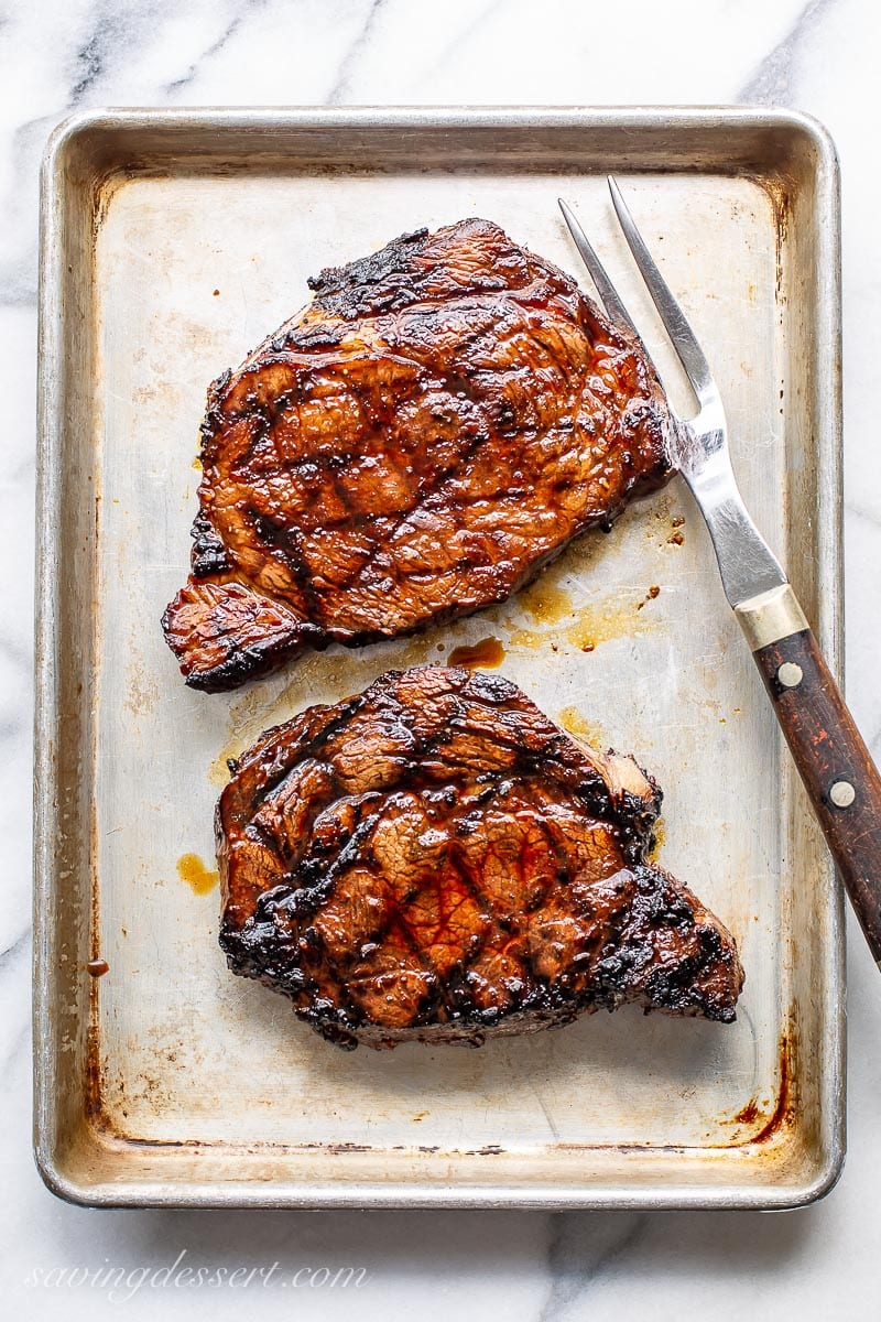Two grilled ribeye steaks on a small baking pan with a large fork