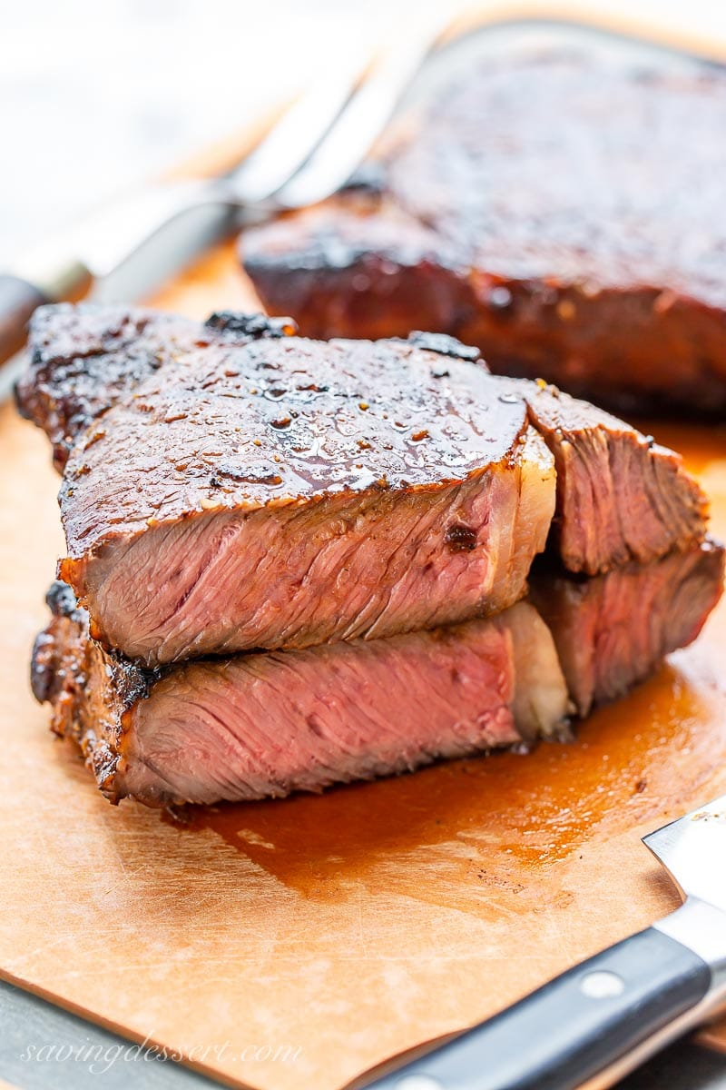A grilled ribeye steak cut in half and stacked on a cutting board, to show the pale pink interior and juicy texture