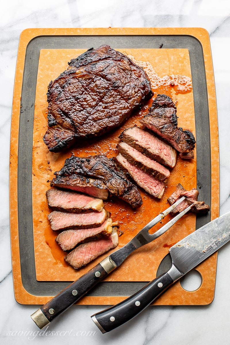 A cutting board with two grilled ribeye steaks, one sliced