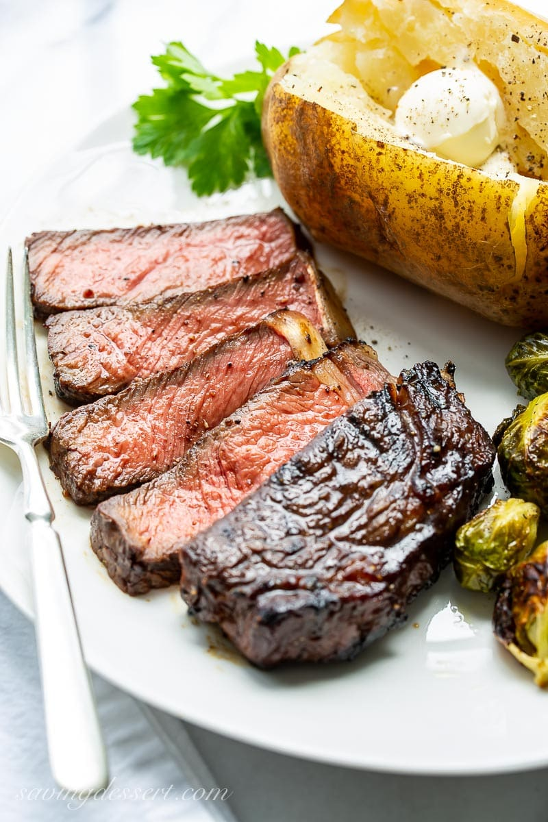 A dinner plate with a sliced ribeye steak with a baked potato and roasted Brussels sprouts.