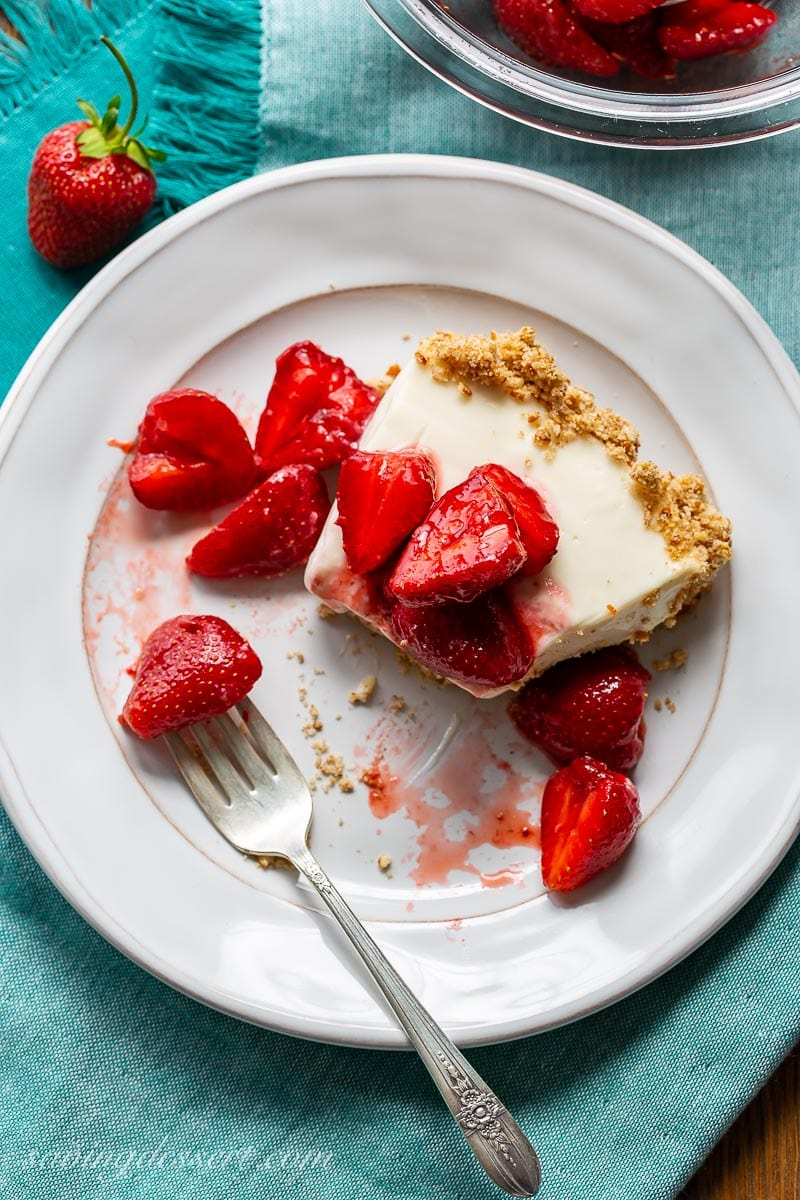 A half eaten slice of pie topped with strawberries