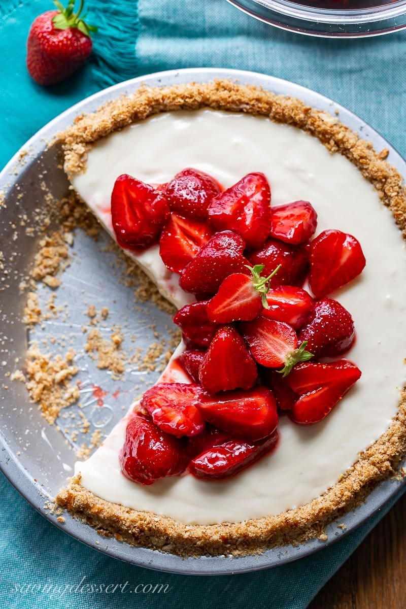 An overhead view of a sliced strawberry cream cheese pie with strawberries on top
