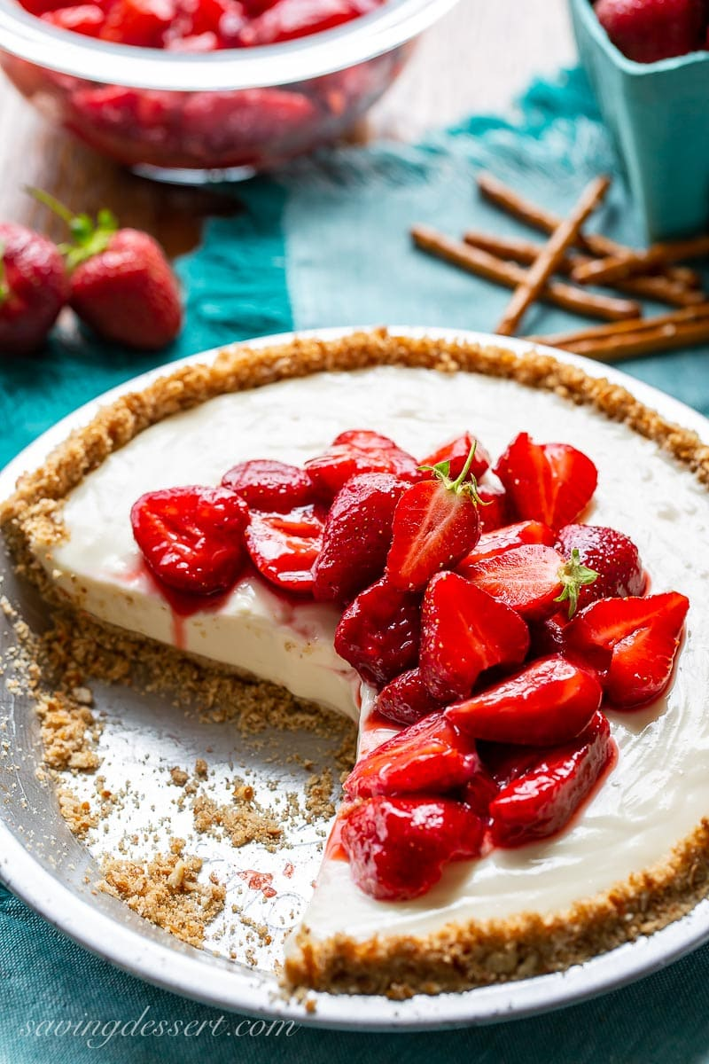 A sliced cream cheese pie topped with ripe, sliced strawberries